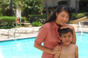 a mother and son next to a pool.