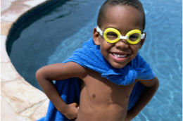 a young boy with goggles and a towel around his neck like a cape.