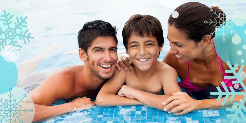 a mother and father with their child smiling by the edge of a pool.