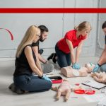 a group of young adults learning CPR.