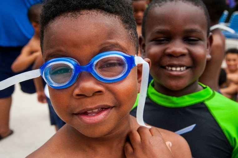 closeup of two boys, one wearing blue googles.