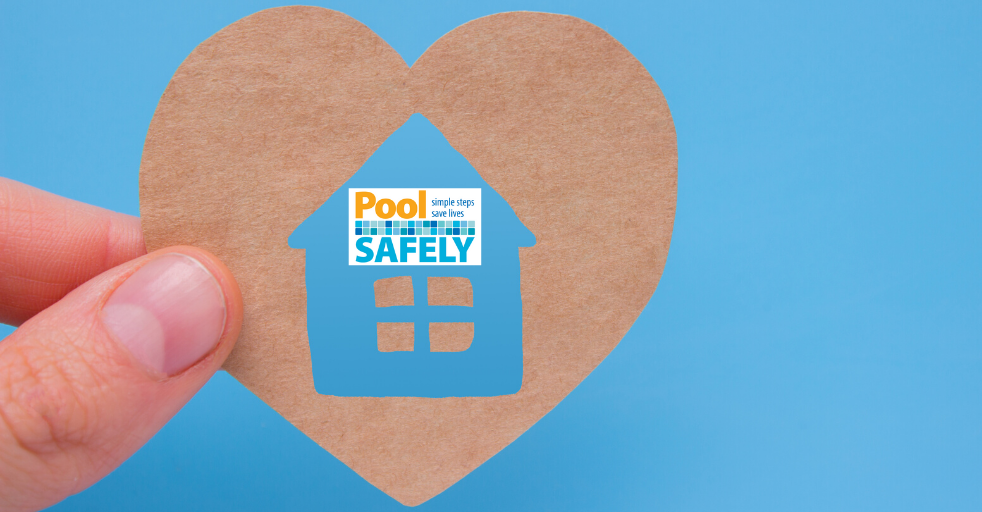 closeup of a person holding a heart shape with a house inside that has the pool safely logo on it.