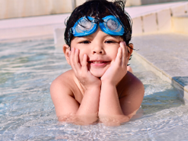 young boy with his head in his hands in a pool.