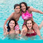two moms with their kids on their shoulders in a pool.