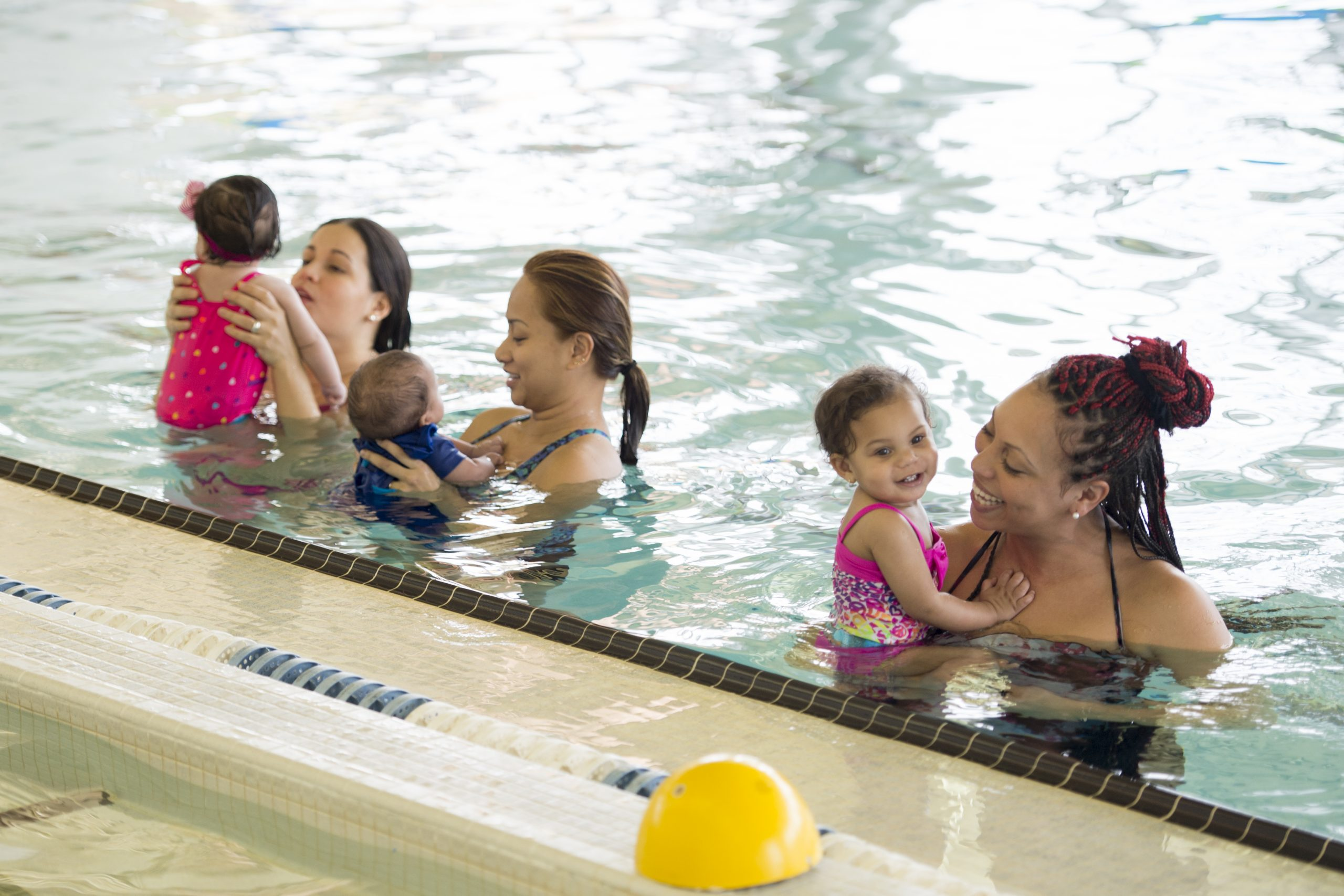 A group of mothers are at the pool and are introducing their young babies to the water at the pool. They are standing in a row and are holding their children.