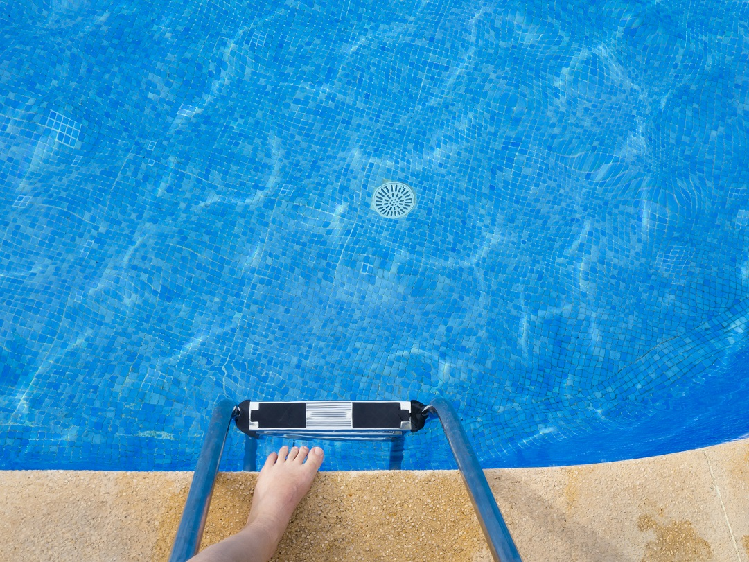 PoV at the edge of a swimming pool, looking down into the water with own feet at the edge of the pool.