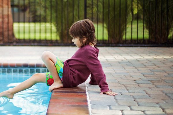 A child sitting by the edge of a pool dipping one foot in.