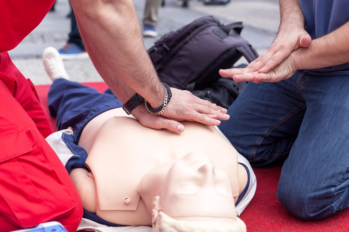 Instructor Teaching Cpr On Dummy.