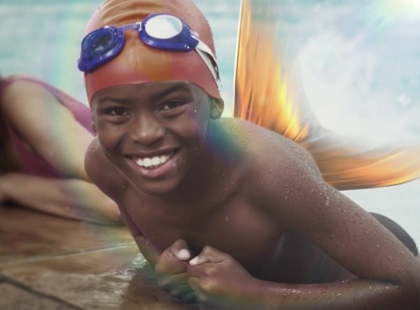 a young boy resting on the edge of a pool with gold fins coming from his back.