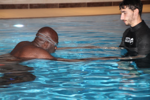 two men in a pool, one with his head down blowing bubbles and one holding his hands and watching.