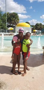 a woman and two younger children at a water park, hugging.